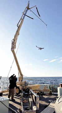 A device called a skyhook uses an elastic cable to snare the wing tip of ScanEagle for retrieval.